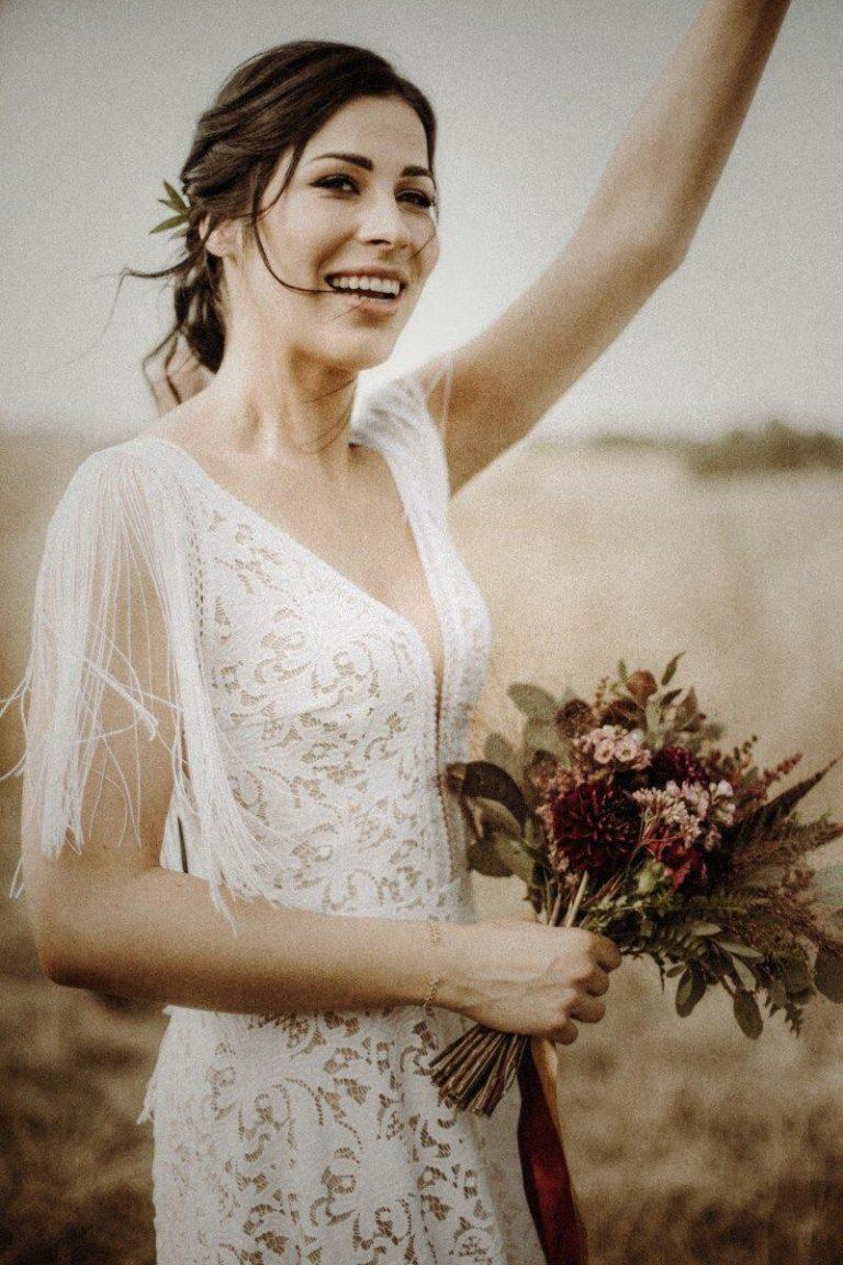 Suknia ślubna w stylu boho Santorini 1 z dodatkowymi frędzlami na ramionach i plecach.