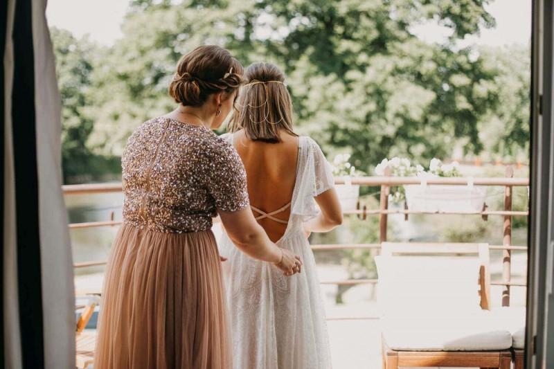 Suknia ślubna w stylu boho Porto 35 z głębiej wyciętymi plecami, dodatkowym paskiem, częściowo zaszytym dekoltem z przodu.