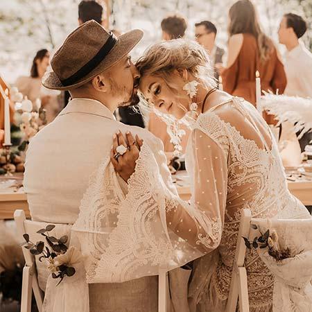para tyłem przy stole- suknia ślubna boho